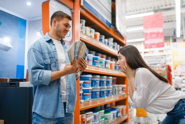 Young couple choosing color with palette in hardware store.