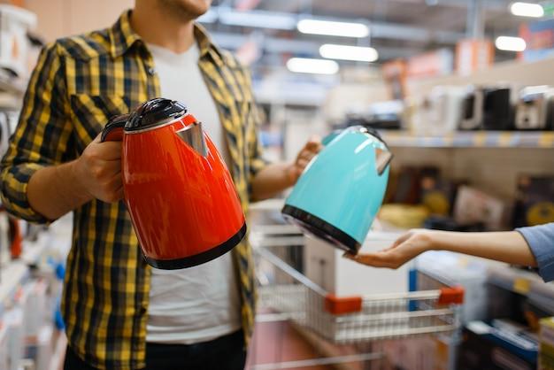 전자 제품 매장에서 전기 주전자를 선택하는 젊은 부부. 남자와 여자는 시장에서 가전 제품을 구입