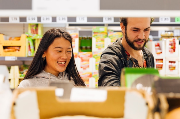 Young couple choosing goods in supermarket