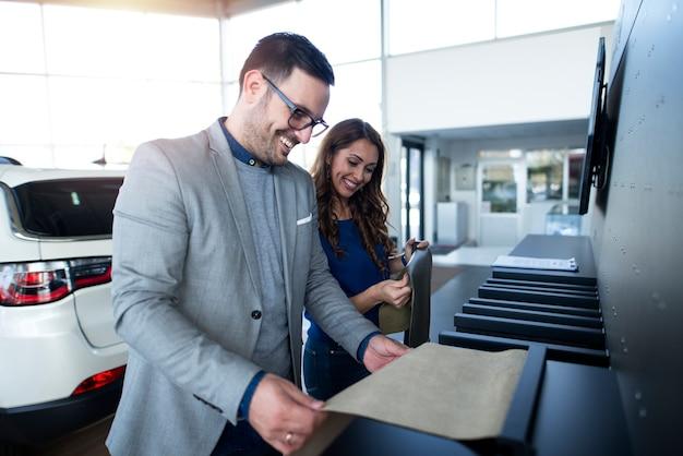 Молодая пара выбирает цвет салона для своего нового автомобиля