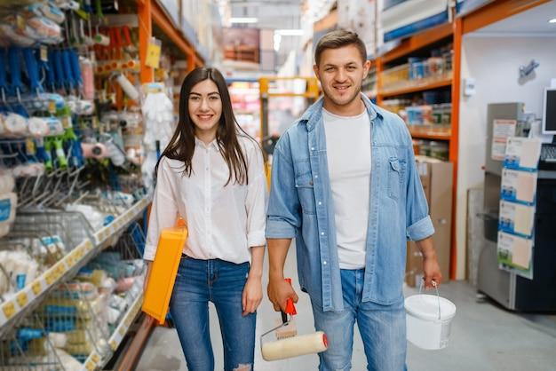 Молодая пара, выбирая валик для рисования