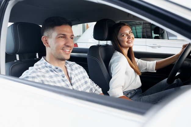 Young couple choosing their new car in a car shop together