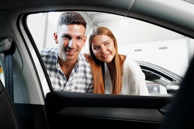 一緒にカーショップで新しい車を選ぶ若いカップル