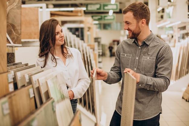 Молодая пара, выбирая плитку на строительном рынке