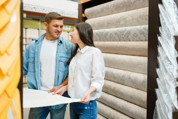 Молодая пара, выбирая обои в хозяйственном магазине