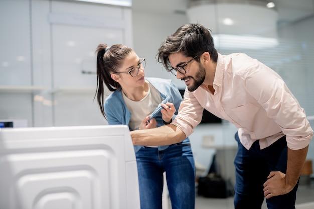 ホワイトウェア部門に立っている間洗濯機を選択する若いカップル。