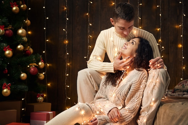 Young couple in christmas decoration and lights