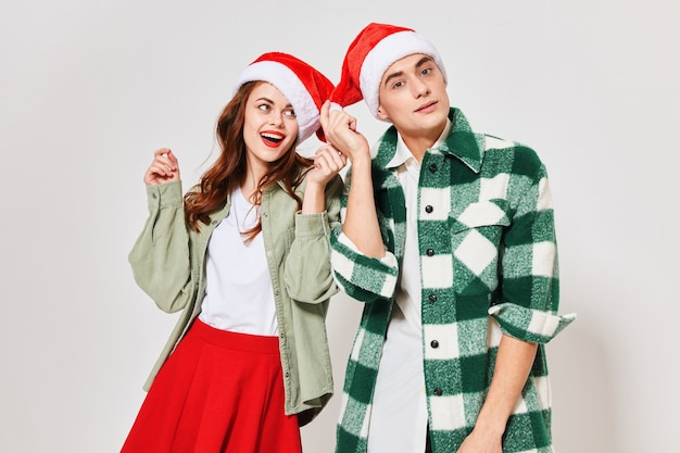 Young couple in christmas hats gestures with their hands.