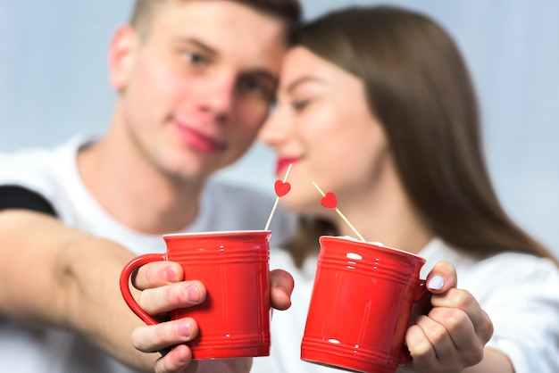 Young couple clanging cups of coffee