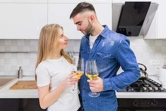 Young couple clanging glasses of wine in kitchen