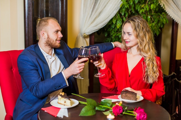 Young couple clanging glasses at table in restaurant