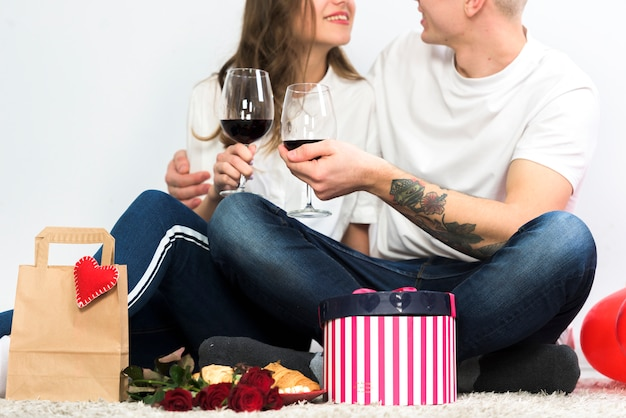 Young couple clanging glasses of wine on floor