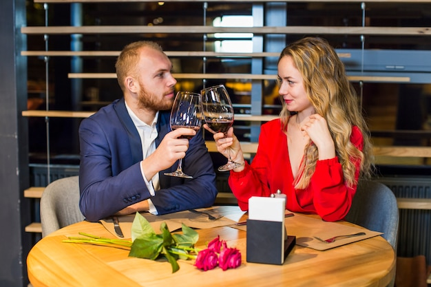 Young couple clanging wine glasses at table in restaurant