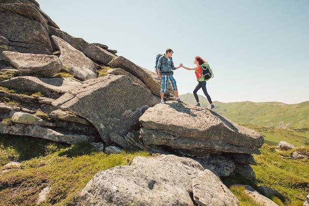 Молодая пара, восхождение в горы