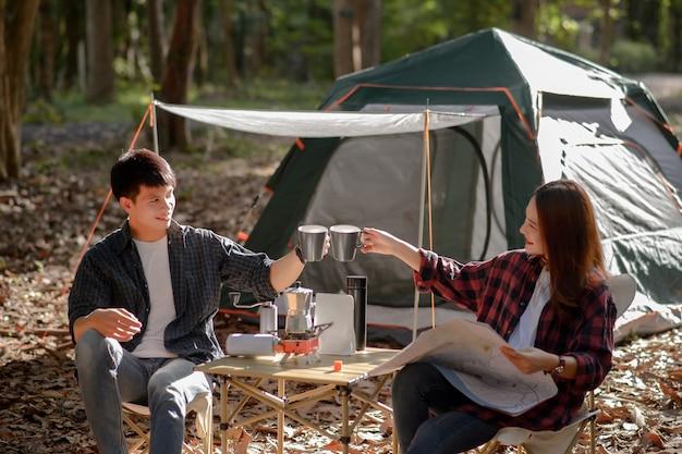 自然公園で朝のキャンプテントの前で朝コーヒーマグを一緒にチリンと鳴らす若いカップル