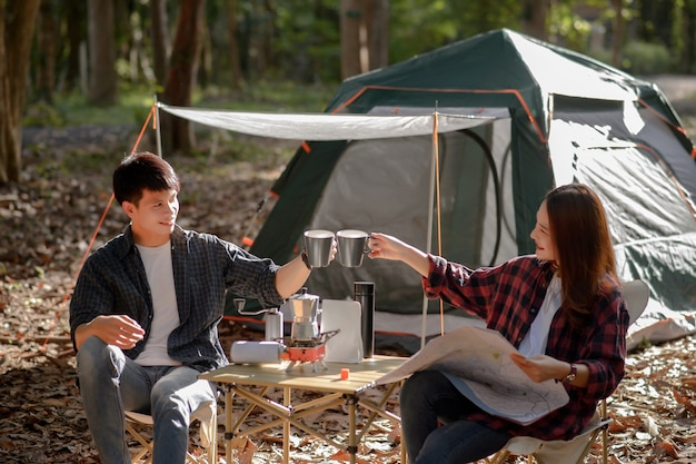 Young couple clinking coffee mugs together in the morning in front of a camping tent in the morning at nature park