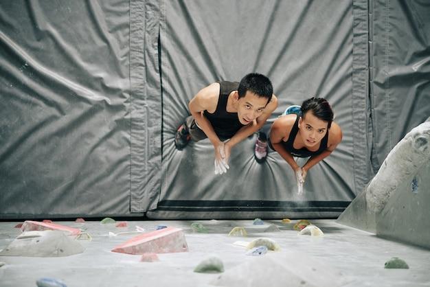 高いボルダリングの壁を見て、上から見たときにパウダーチョークで手をコーティングする若いカップル