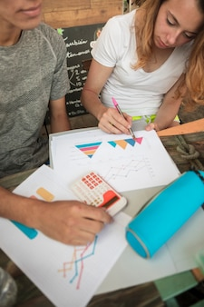 Young couple coloring diagrams on paper