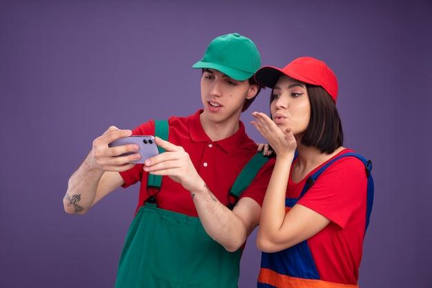 Giovane coppia concentrata ragazzo ragazza seria in uniforme da operaio edile e berretto che si fa selfie insieme ragazza che tiene la mano sulla spalla del ragazzo inviando un bacio