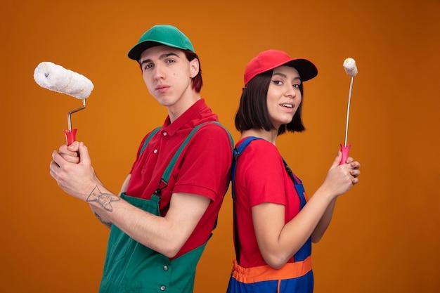 Giovane coppia ragazzo fiducioso e ragazza eccitata in uniforme da operaio edile e berretto in piedi schiena contro schiena tenendo il rullo di vernice guardando la telecamera isolata sul muro arancione