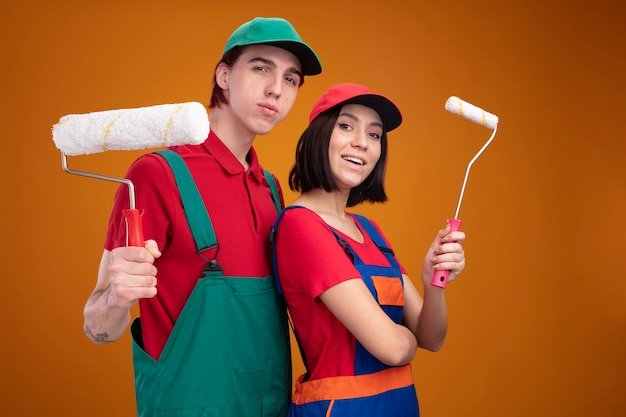 Young couple confident guy and excited girl in construction worker uniform and cap standing in profile view holding paint roller looking at camera isolated on orange wall