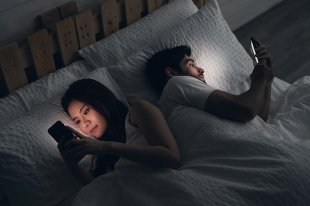 Young couple conflict in bed. happy smiling woman turned her back to man, reading message on mobile phone, trying to peek at screen