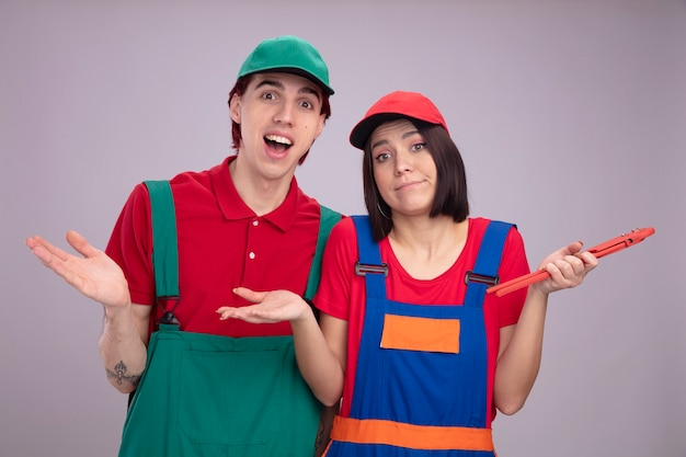 Young couple in construction worker uniform and cap clueless girl holding pipe wrench excited guy both looking at camera showing empty hand isolated on white wall