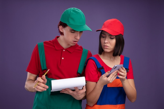 Young couple in construction worker uniform and cap concentrated guy holding pencil and clipboard serious girl holding mobile phone both looking at clipboard isolated on purple wall