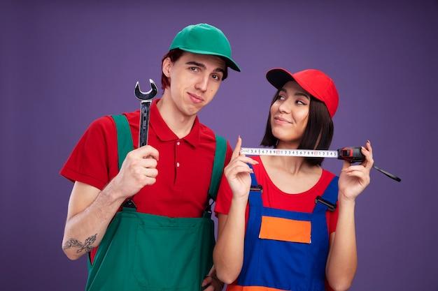 Giovane coppia in uniforme da operaio edile e cappello fiducioso ragazzo con chiave inglese ragazza con metro a nastro guardando ragazzo