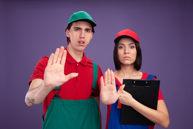 Young couple in construction worker uniform and cap frowning guy serious girl holding pencil and clipboard both looking at camera doing stop gesture isolated on purple wall