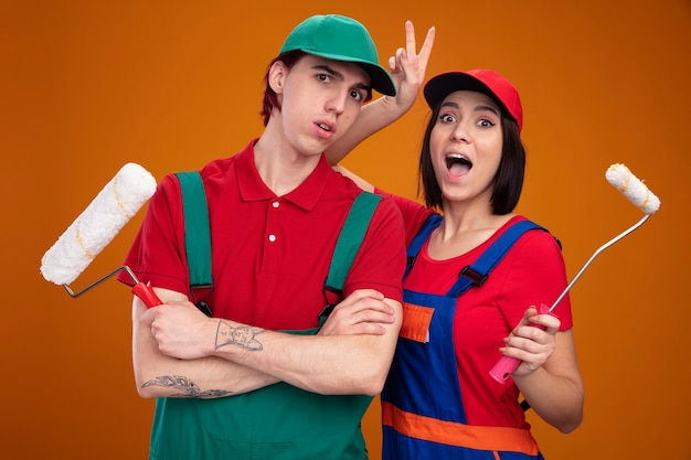 Young couple in construction worker uniform and cap holding paint roller  surprised guy standing with closed posture excited girl making bunny ears behind guys head