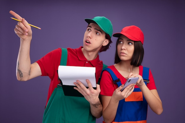 Young couple in construction worker uniform and cap impressed guy holding pencil and clipboard pointing up serious girl holding mobile phone both looking up isolated on purple wall