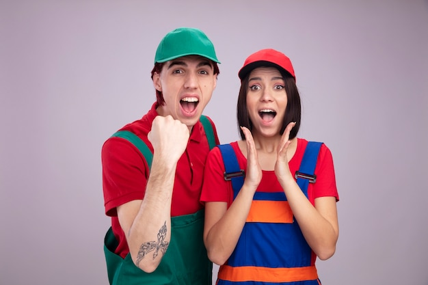 Young couple in construction worker uniform and cap joyful guy doing yes gesture excited girl keeping hands in air both looking at camera isolated on white wall