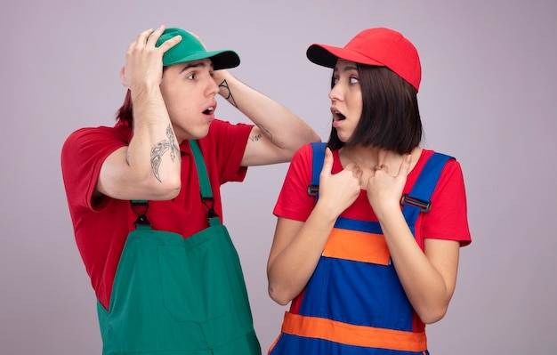 Young couple in construction worker uniform and cap looking at each other concerned guy keeping hands on head surprised girl pointing at herself isolated on white wall