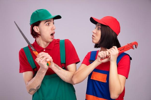 Giovane coppia in uniforme da operaio edile e berretto che si guardano combattendo un ragazzo spaventato che tiene la mano ha visto una ragazza aggressiva che tiene una chiave a tubo isolata sul muro bianco
