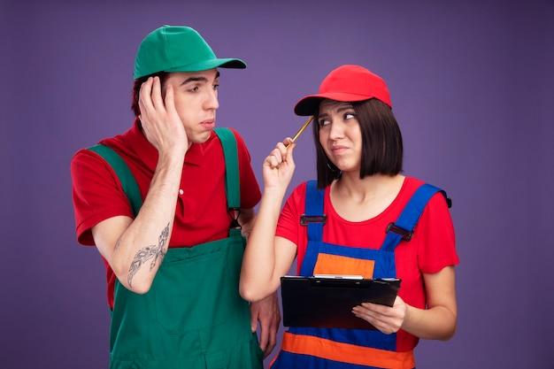 Coppia giovane in operaio edile uniforme e berretto guardando a vicenda ragazza sgradita tenendo la matita e appunti toccando la testa con la matita in questione ragazzo tenendo la mano sulla testa