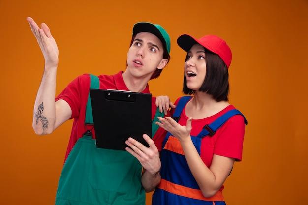 Giovane coppia in uniforme da operaio edile e berretto guardando di lato che mostra la mano vuota ragazzo sorpreso ragazza eccitata che tiene la mano sulla spalla del ragazzo