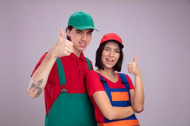 Giovane coppia in uniforme da operaio edile e berretto sorridente ragazzo ragazza gioiosa che guarda l'obbiettivo che mostra pollice in su ragazza che strizza l'occhio isolata sulla parete bianca con lo spazio della copia