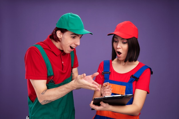 Young couple in construction worker uniform and cap surprised girl holding pencil and clipboard excited guy pointing with hands at clipboard both looking at clipboard