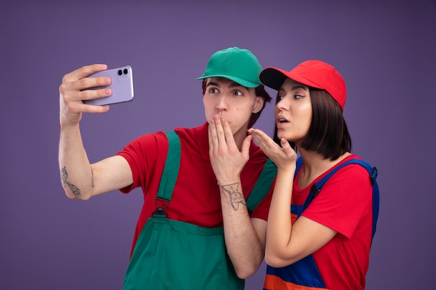 Young couple in construction worker uniform and cap taking selfie together concerned guy keeping hand on mouth confident girl sending blow kiss looking at guy isolated on purple wall