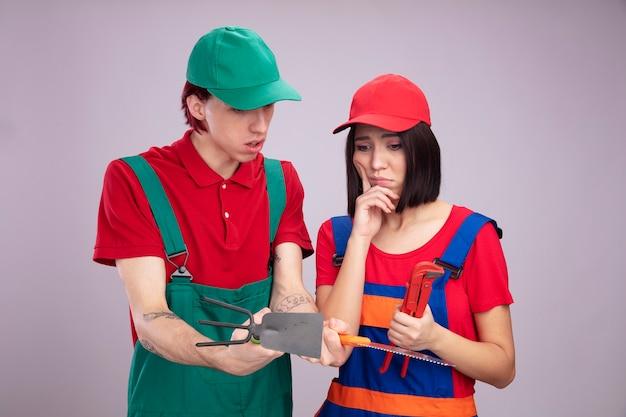 Giovane coppia in uniforme da operaio edile e berretto premuroso ragazza con chiave a tubo che mostra hoerake e sega a mano alla ragazza e lei tenendo la mano sul mento sia guardando gli strumenti di costruzione