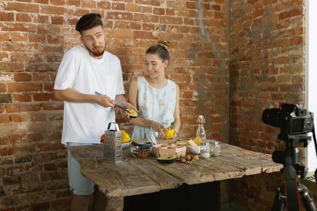 若いカップルが調理し、vlogやソーシャルメディアのライブビデオを録画する