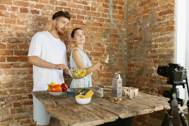 若いカップルがvlogやソーシャルメディアのライブビデオを料理して録画する