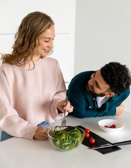 一緒に家で料理をする若いカップル