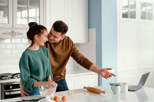 Молодая пара готовит дома