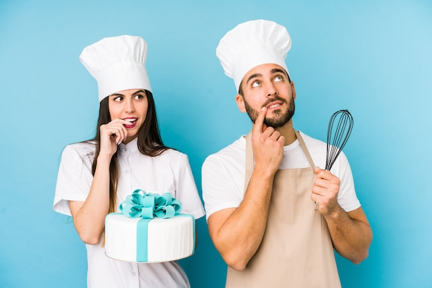 Young couple cooking a cake together isolated relaxed thinking about something looking at a copy space.