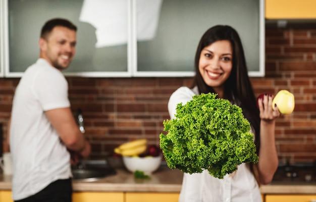 부엌에서 요리하는 젊은 부부. 웃 고, 양상추와 사과 들고 여자입니다. 백그라운드에서 남자. 건강한 식생활.