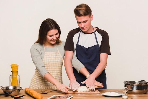 Giovani coppie che cucinano insieme in cucina
