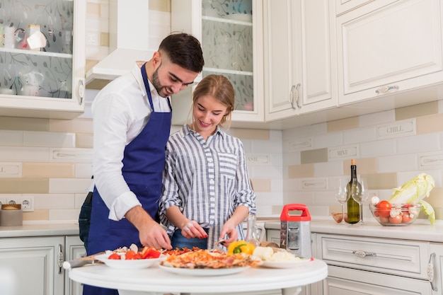 Young couple cooking pizza in kitchen
