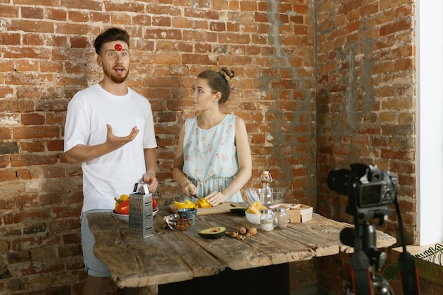 Young couple cooking and recording live video for vlog and social media